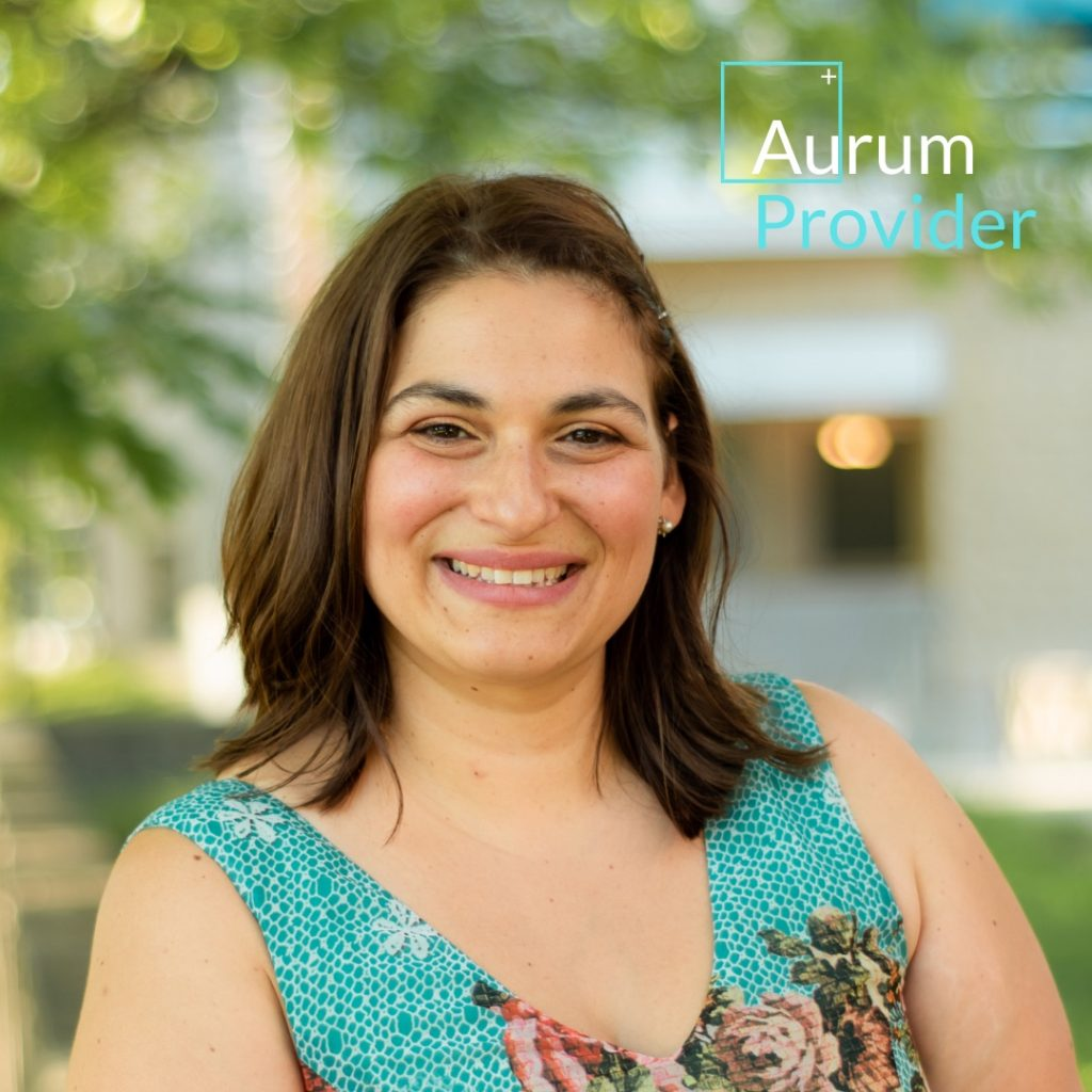 Photo of Dr. Antonia Tsallas MSc ND with teal blue dress outdoors in front of trees. Aurum Provider logo in the top right hand corner of image in white and teal blue font